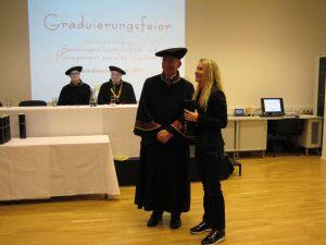 Martina empfängt das Dokument Master of Sience bei der Graduierugsfeier