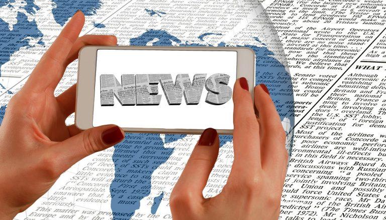 2 Hände halten Handy auf dem News steht